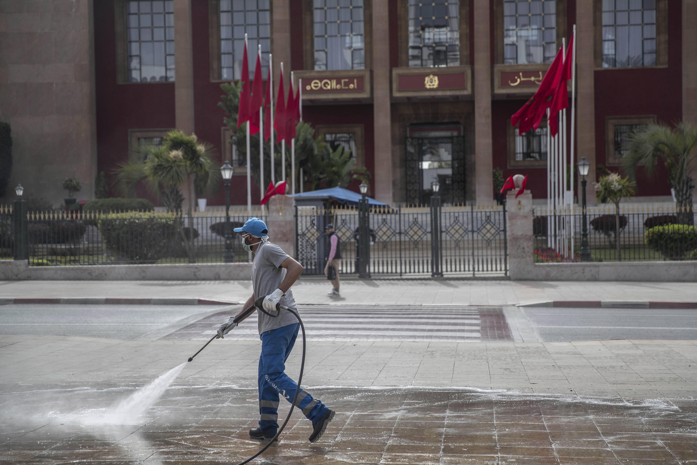 Un homme désinfecte les alentours du Parlement à Rabat, le 18 mars 2020, pour prévenir la propagation de l'épidémie de coronavirus au Maroc.