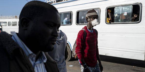 Au Sénégal, des voyageurs se protègent de l'épidémie de coronavirus, à Dakar, le 24 mars 2020.