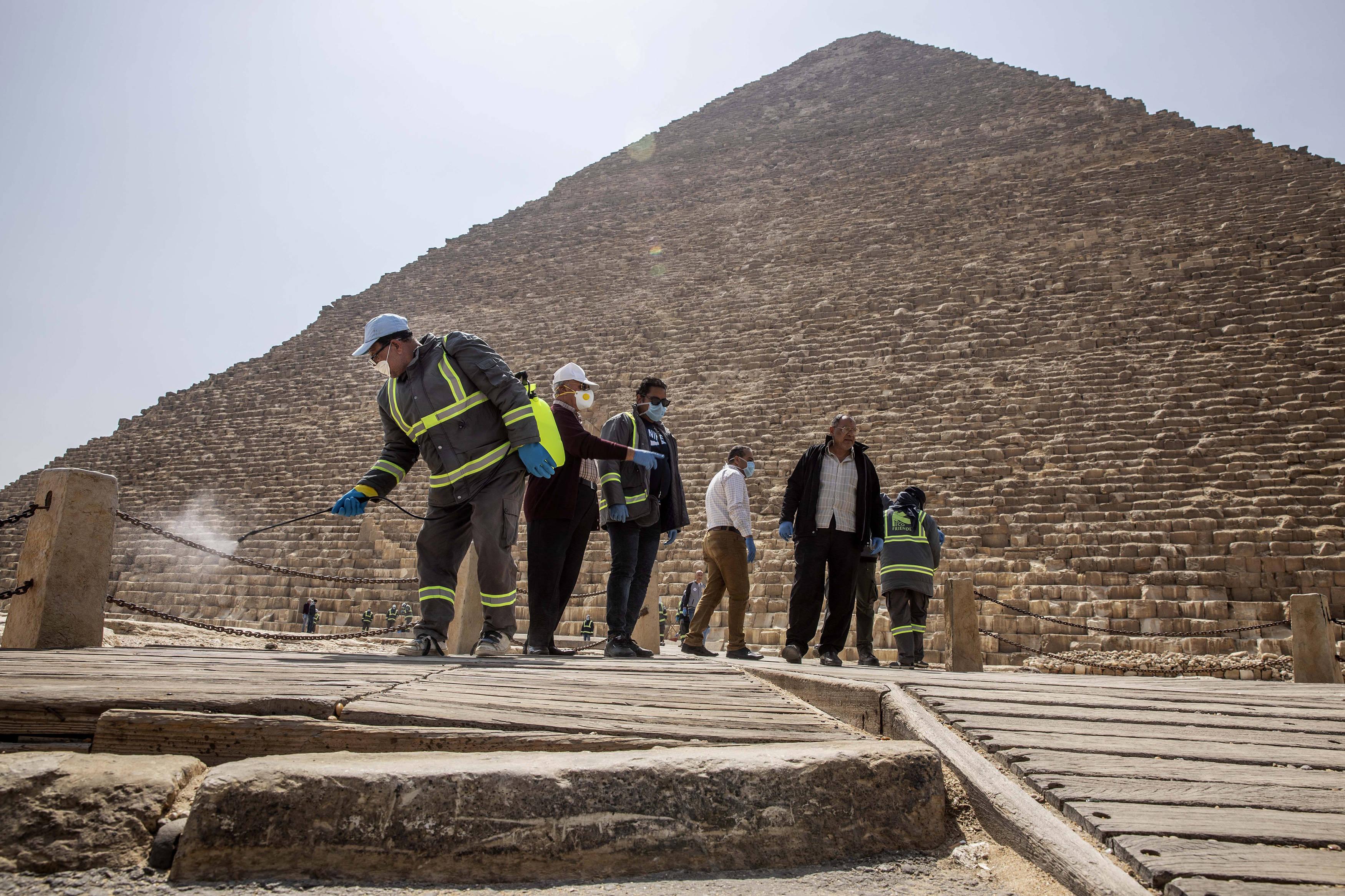 Des agents municipaux près des pyramides Gizeh, le 25 mars 2020.