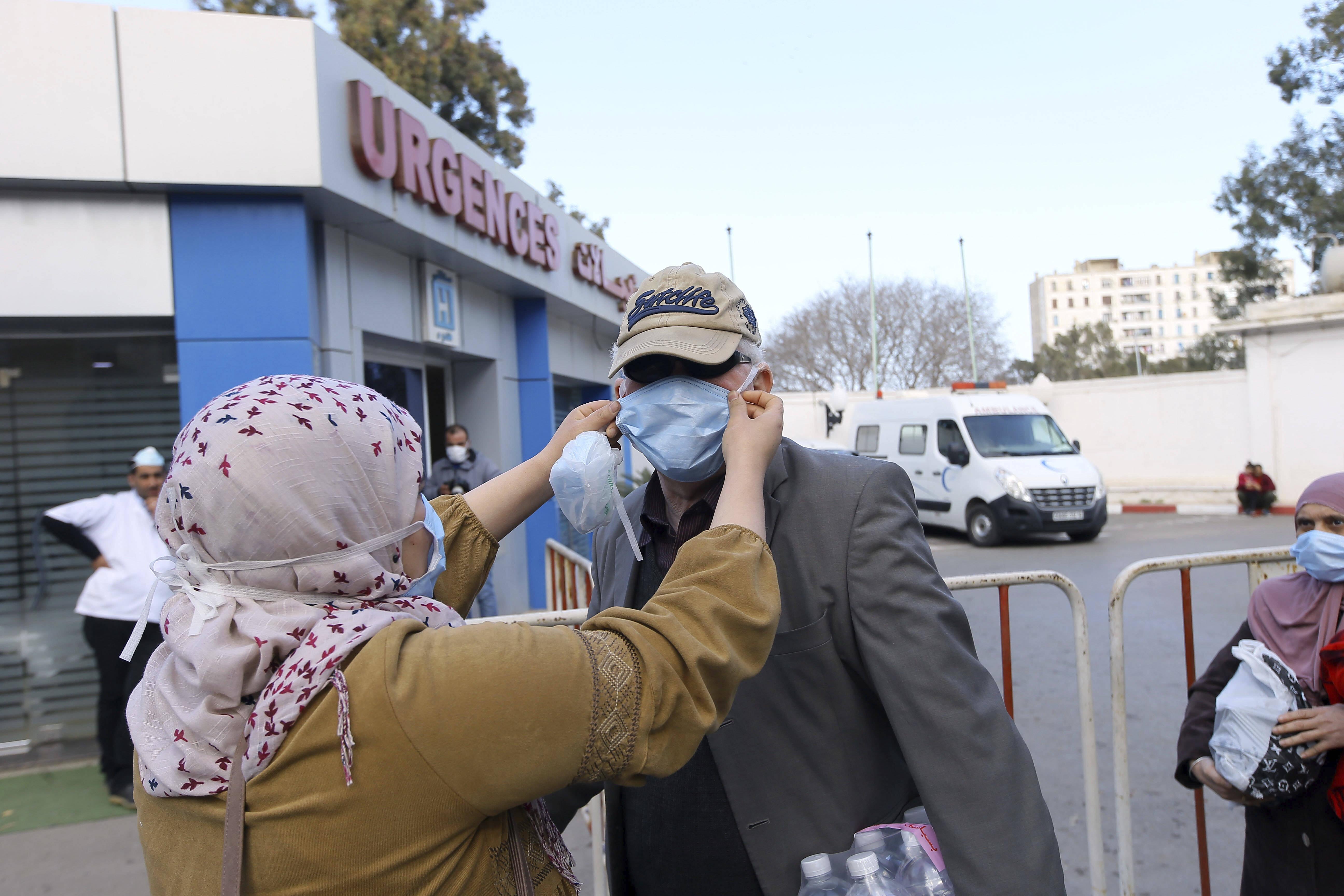 Des personnes portant des masques se tiennent à l'extérieur d'une clinique, à Alger, le 26 février 2020.