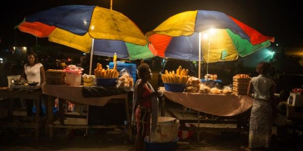 Des femmes proposent des repas chauds sur des étals de rues typiques, la nuit sur le boulevard du 24 novembre à Kinshasa, en 2014. (Archives / illustration)