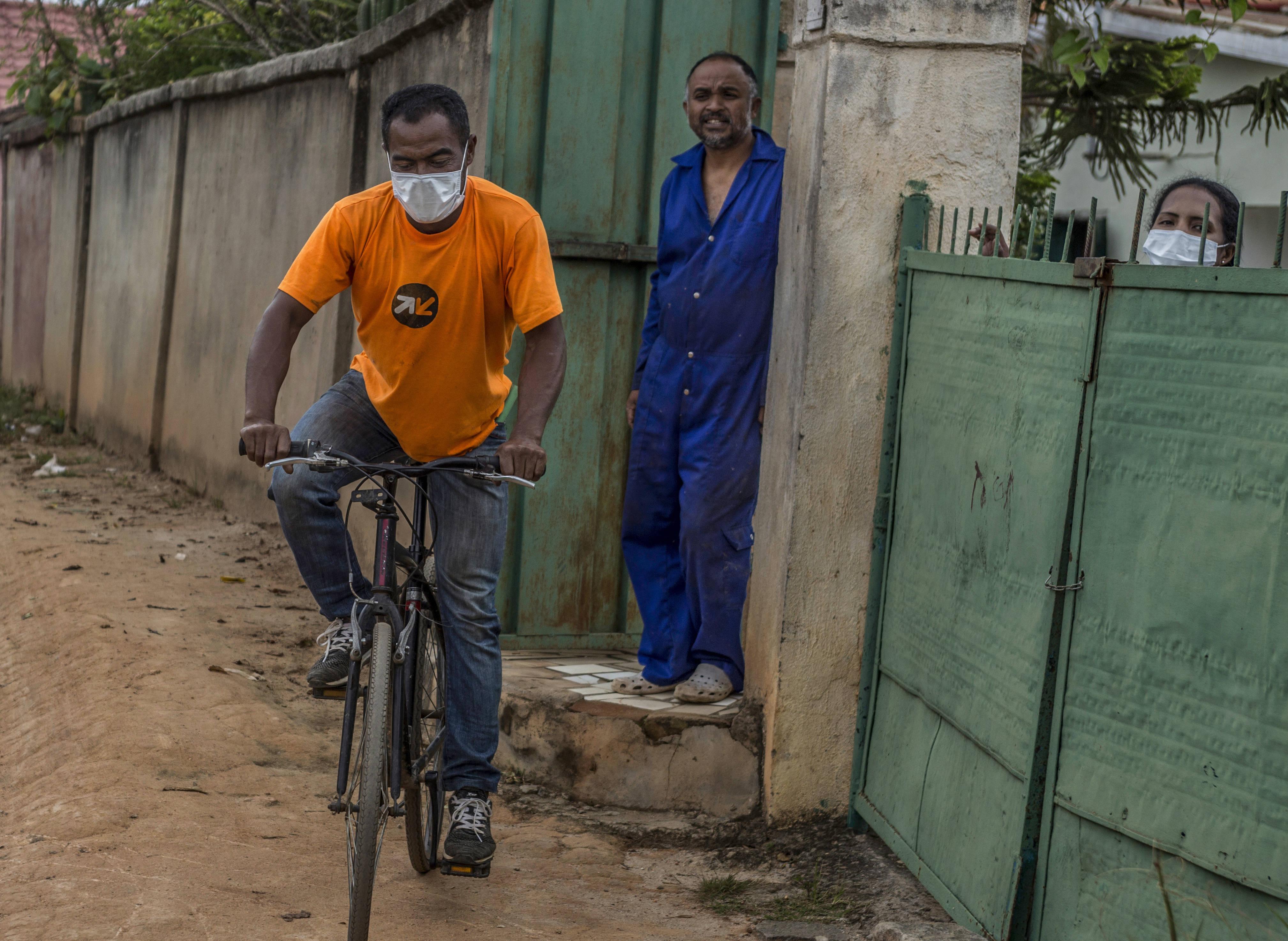 Un cycliste porte un masque pour se protéger du coronavirus, dans une rue d'Antananarivo, le 22 mars.