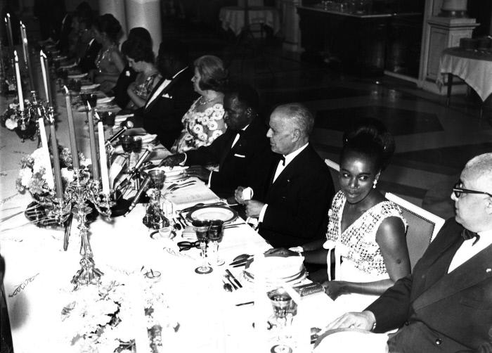 A l'occasion du voyage de Félix Houphouët-Boigny en Tunisie, en 1968, un banquet est offert par Habib Bourguiba à ses invités. On reconnait de droite à gauche : Bahi Ladgham, ministre tunisien de la Défense, Thérèse Houphouët-Boigny, Habib Bourguiba, Félix Houphouët-Boigny, Wassila Bourguiba.