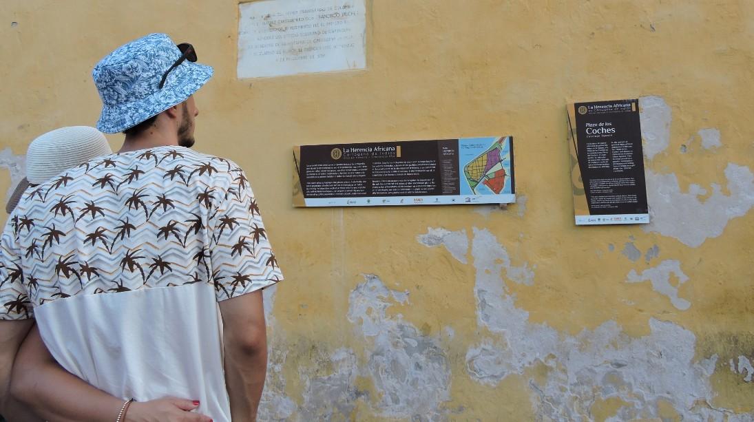Des touristes s'arrêtant devant un panneau d'information du circuit de l'héritage africain à Carthagène
