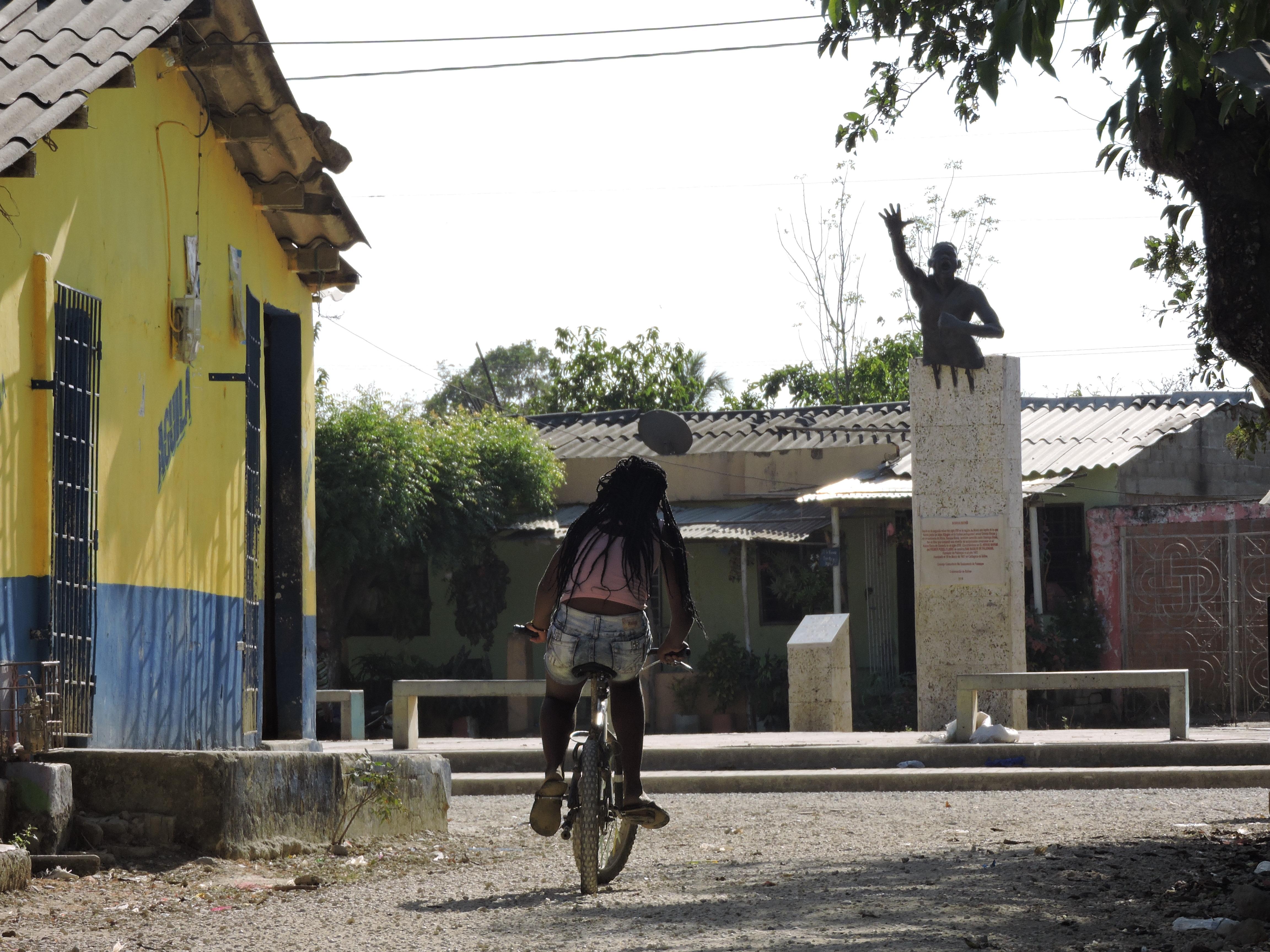 Une jeune fille en vélo sur la place principale du village où trône la statue du héros des afrocolombiens Benko Bioho