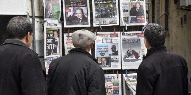 Algériens lisant les unes des journaux devant un kiosque d'Alger, le 11 février 2019.
