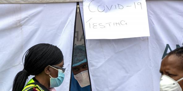 Du personnel médical devant une tente à l'intérieur de laquelle ils procèdent à des dépistages, le 8 avril 2020, à Johannesburg.