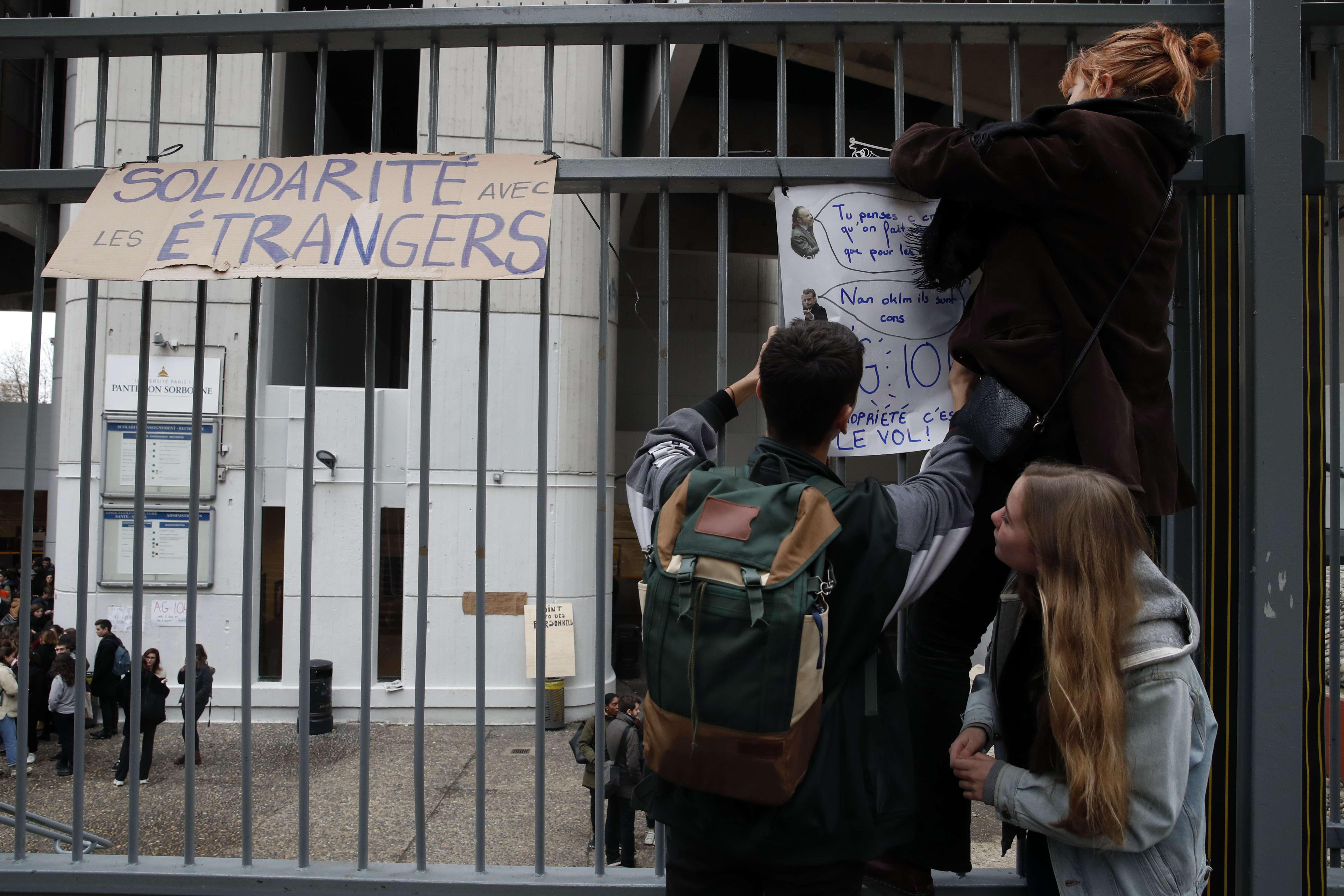 """Des étudiants collent des affiches, dont l'une porte le titre """"Solidarité avec les étrangers"""", sur la clôture de l'université fermée de Tolbiac à Paris, le 5 décembre 2018."""