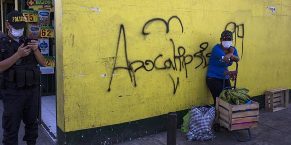 Une femme masquée attend avec ses achats à côté d'une inscription murale «Apocalypse» à Lima, au Pérou, le 19 mars.