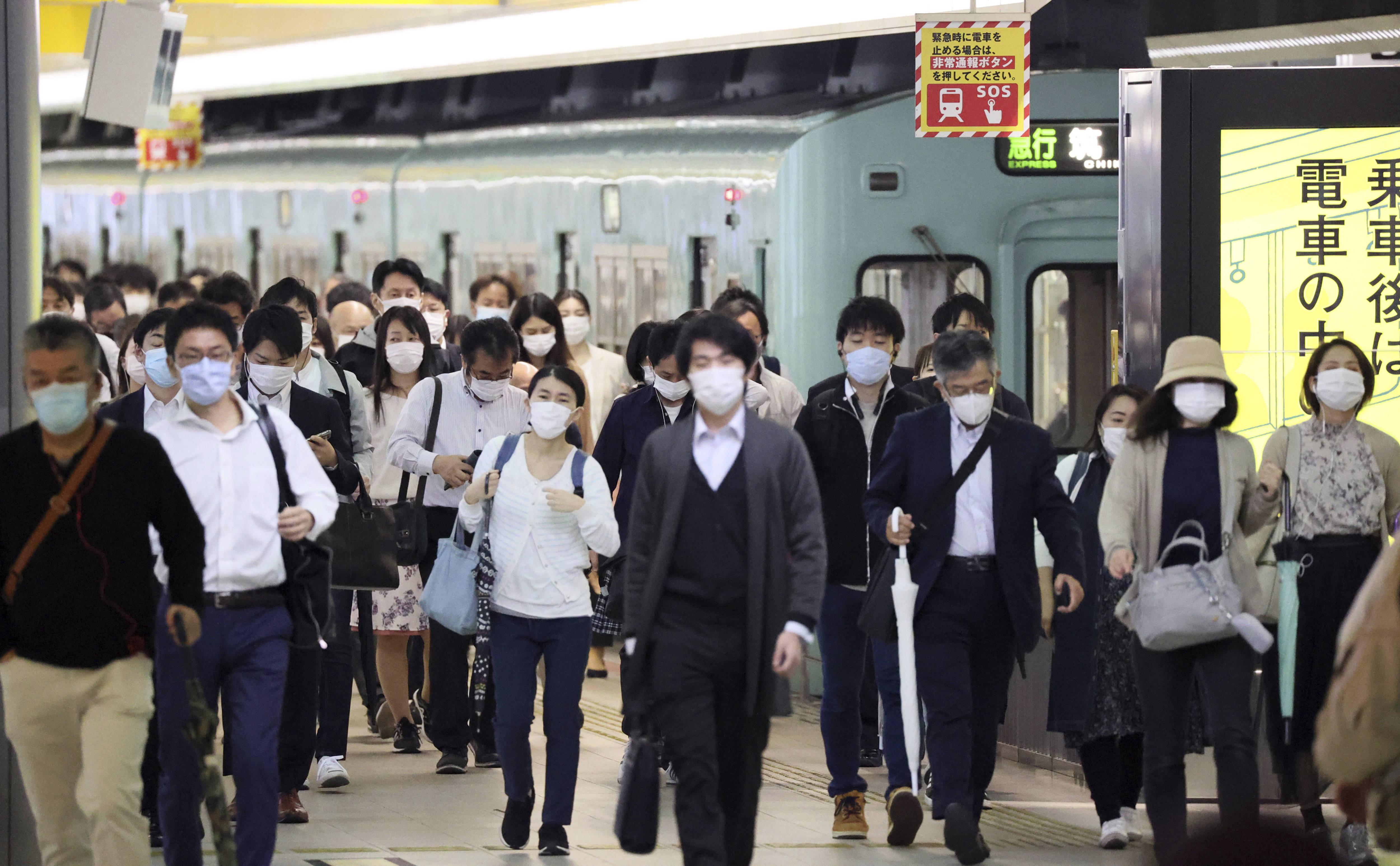 Des personnes portant un masque se rendent au travail à Fukuoka, au Japon, le 15 mai.