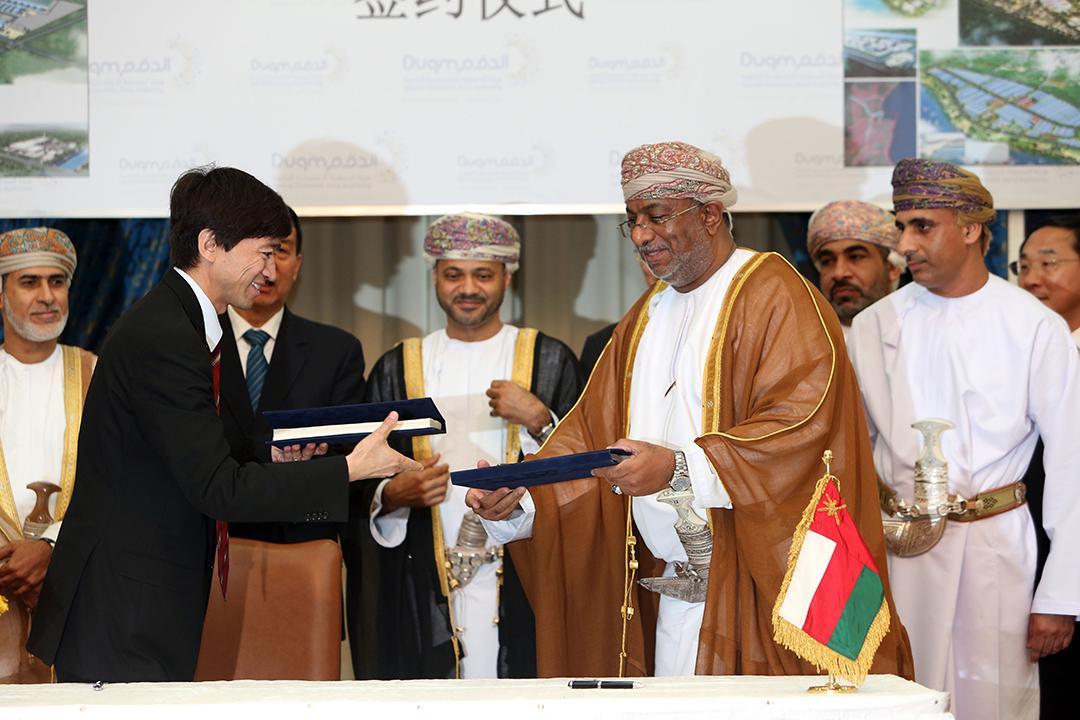Yahya bin Said bin Abdullah Al-Jabri, ministre de l'Autorité des zones économiques spéciales omanais et le chinois Ali Sha, PDG d'Oman Wanfang L.L.C se serrent la main après avoir signé un accord économique le 23 mai 2016 à Mascate.