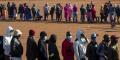 Des personnes touchées par le ralentissement économique dû au coronavirus COVID-19 font la queue pour recevoir des dons de nourriture, au sud-ouest de Pretoria, le 20 mai 2020.