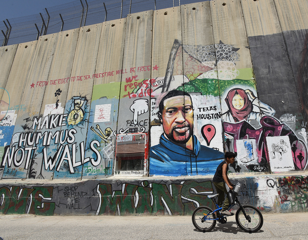 A Palestinian Rides A Bicycle Past A Graffiti Mural Of George Floyd In Bethlehem, West Bank Floyd, 46, an unarmed African American, died on May 25, in Minneapolis, Minnesota, after a white police officer Derek Charvin forcefully knelt on his neck for nearly nine minutes while Floyd pleaded that he couldn't breathe.<br srcset=