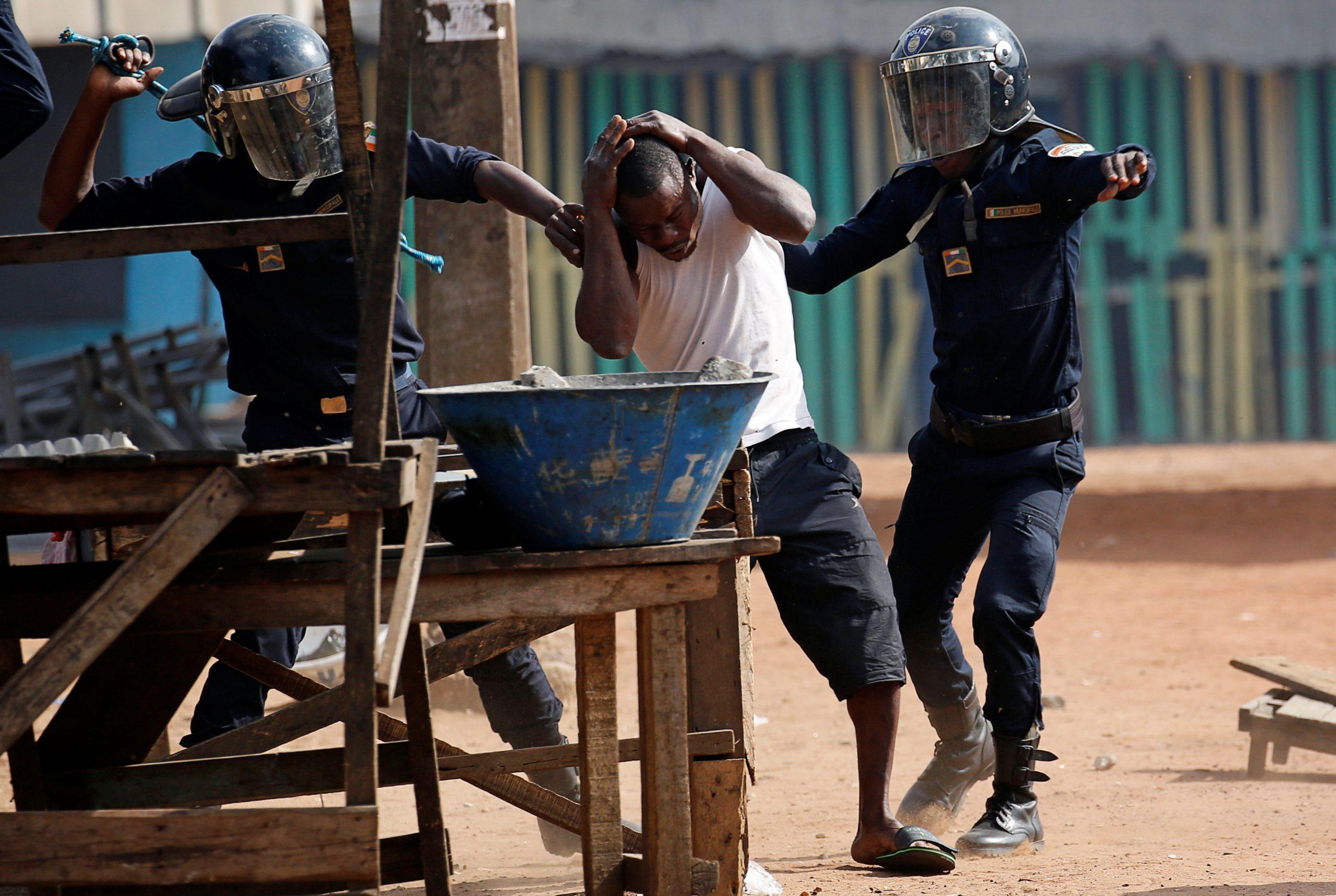 Des policiers interpellent un manifestant lors des rassemblements contre une nouvelle candidature d'Alassane Ouattara, à Abidjan le 13 août 2020.