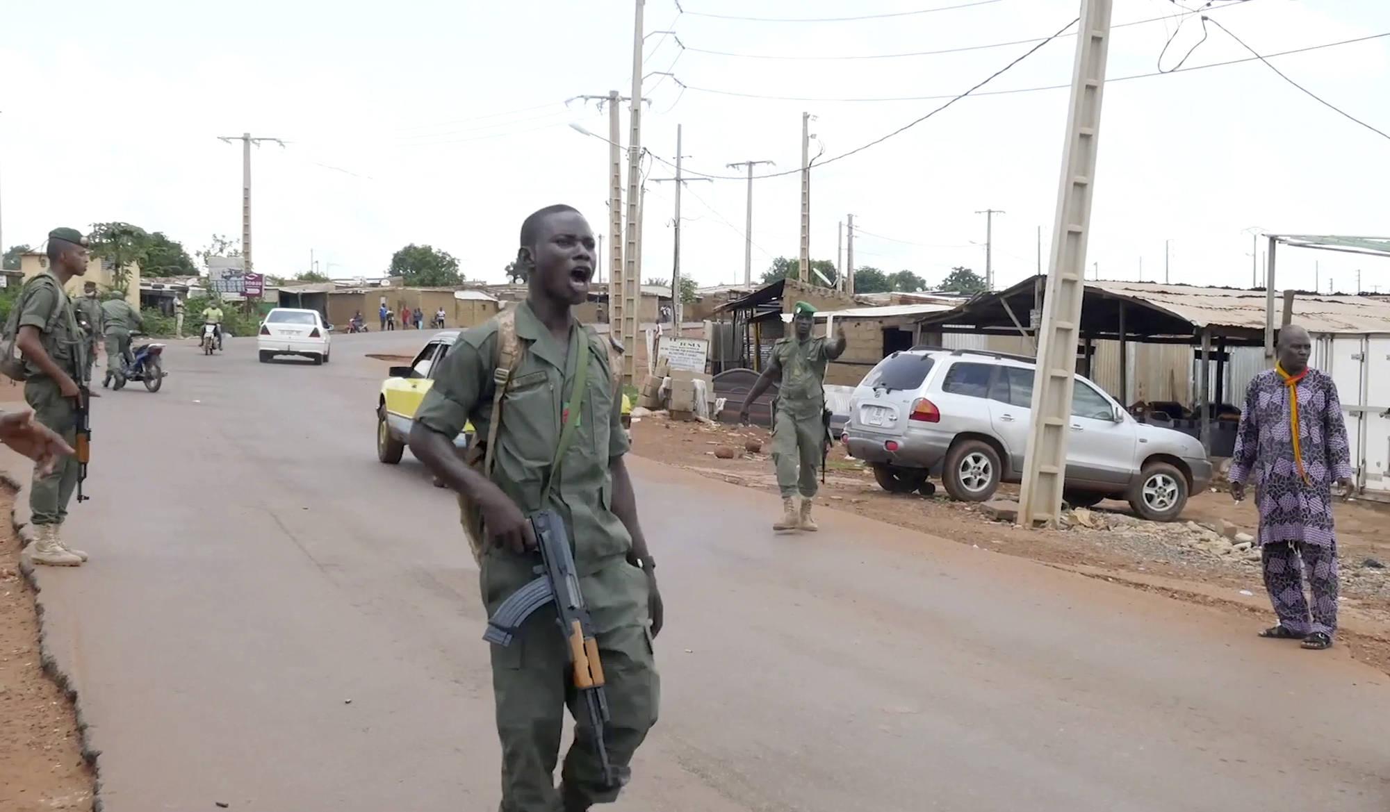 Un militaire malien, membre présumé des mutins du camp militaire de Kati, contrôle la circulation à proximité du camp militaire situé à 15 km de Bamako, le 18 août 2020.