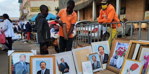 Le Camerounais Agatha Moses (au centre), doyen de la vente des portraits du président Paul Biya, avenue Kennedy, à Yaoundé.