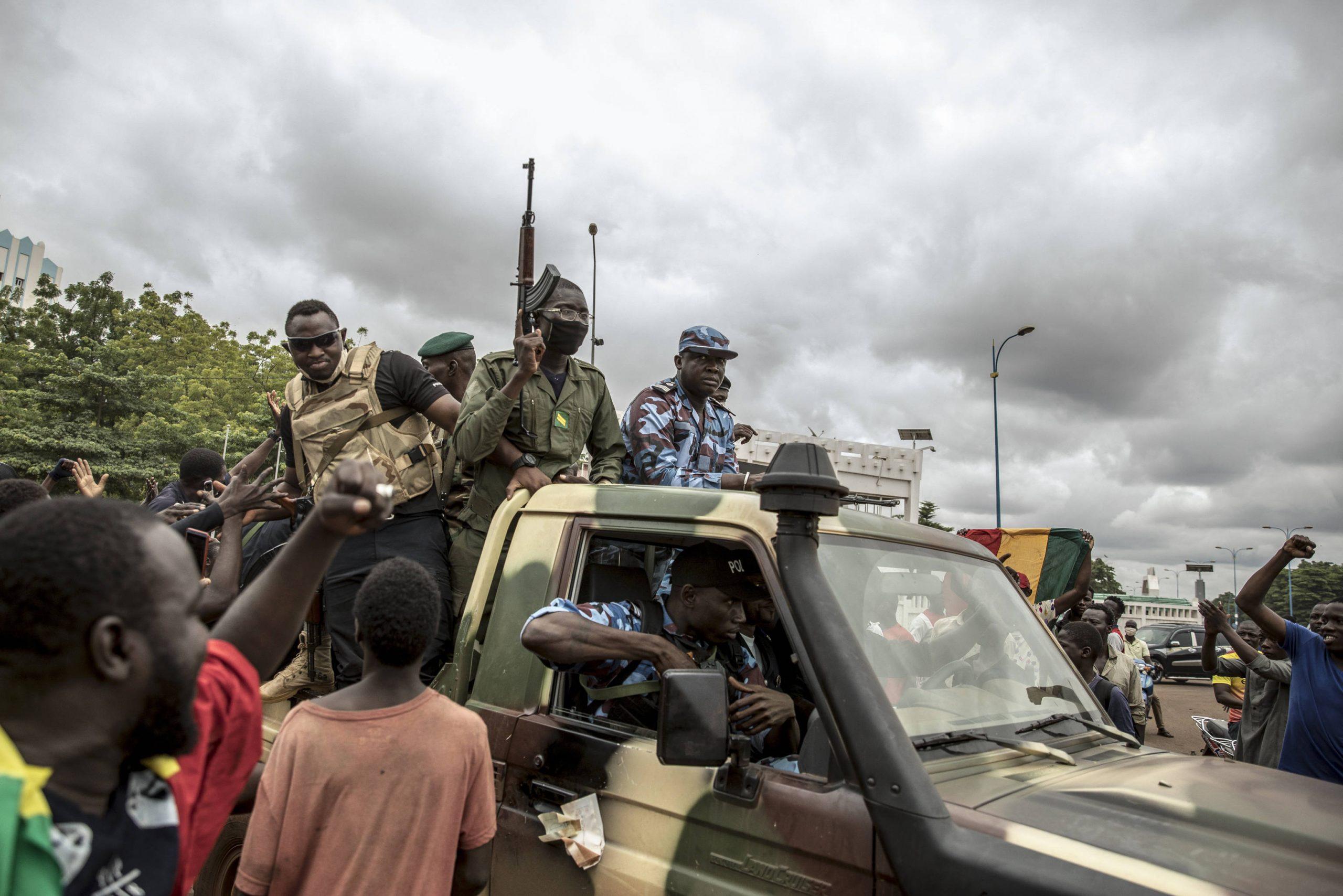 Des manifestants saluent le passage un convoi de militaires à Bamako, le 19 août 2020, au lendemain de la démission d'IBK.