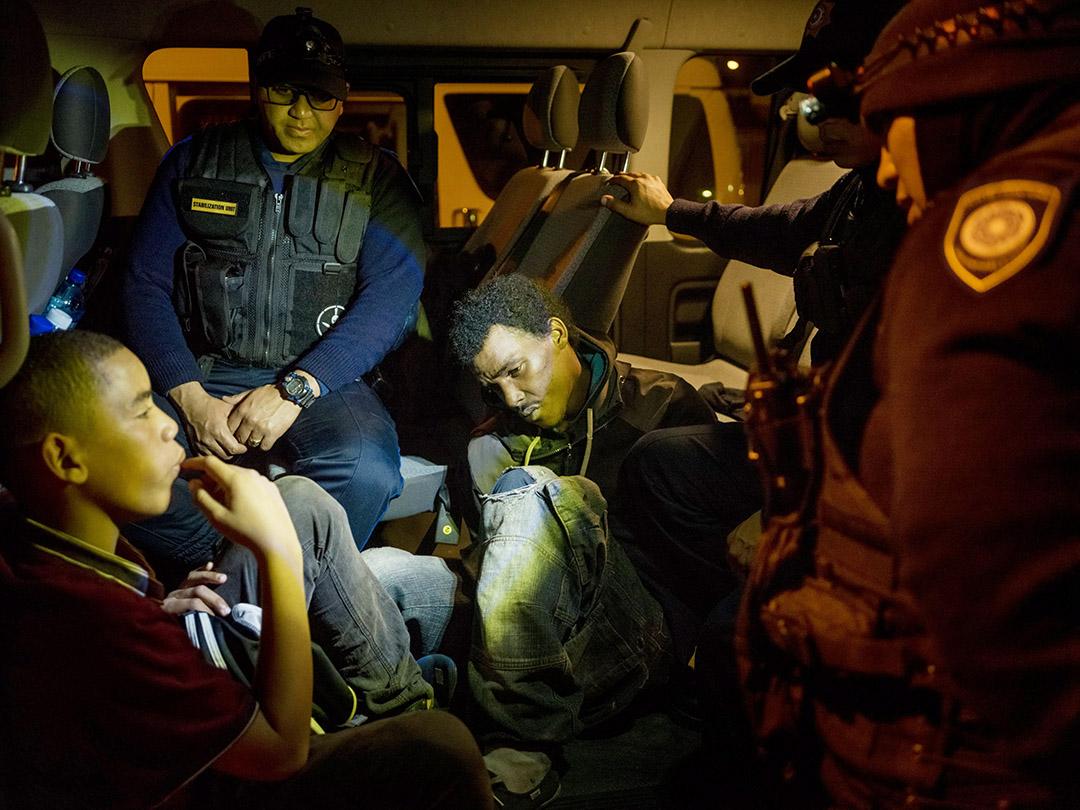 Un homme soupçonné de posséder de la drogue est emmené au poste par des policiers sud-africains.