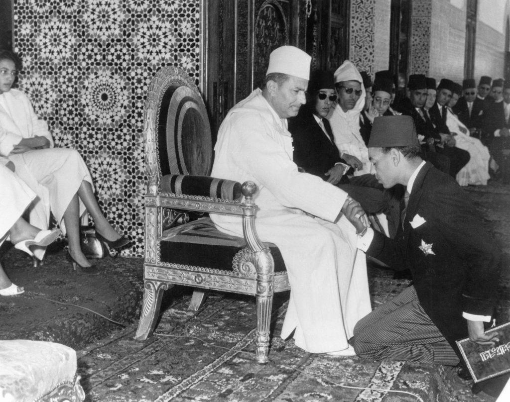 Hassan II (alors prince héritier), agenouillé devant son père, le roi Mohammed V, en 1957.
