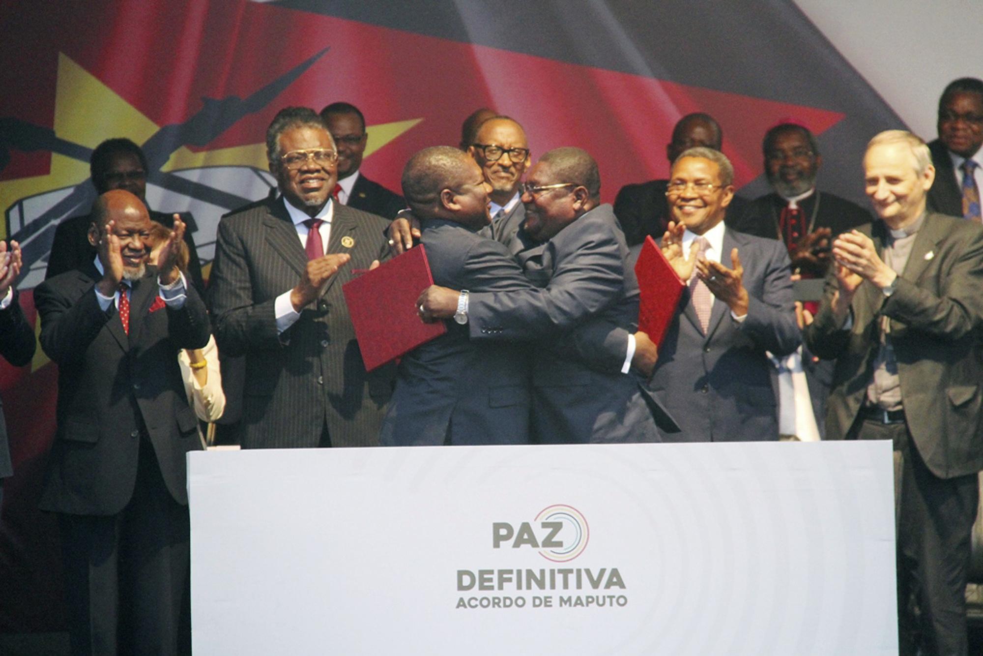 Le président mozambicain Filipe Nyusi (au centre, à gauche) et le leader de la Renamo, Ossufo Momade, s'embrassent lors de la signature des accords de paix à Maputo, au Mozambique, le 6 août 2019.