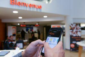 Un employé Orange manipule l'application Orange Money dans une boutique de Casablanca.
