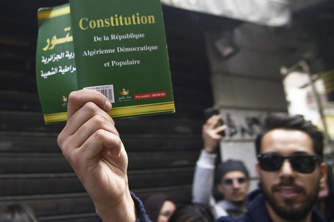 Un manifestant algérien brandit un tract ldemandant la réforme de la Constitution, posant le carde d'un État civil, non militaire.