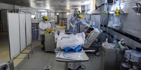 Des infirmières prodiguent des soins à un patient intubé, dans une unité de soins intensifs à l'hôpital de la ville de Gabès, dans le sud-ouest de la Tunisie, le 26 août 2020.