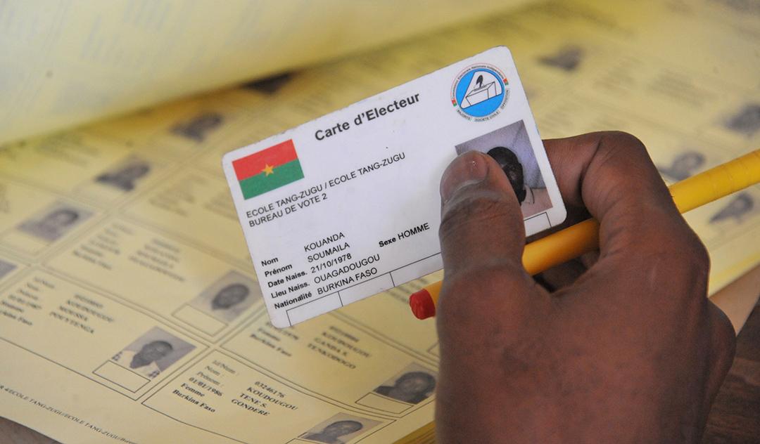 Un électeur présente sa carte, lors des élections municipales de 2016, à Ouagadougou.