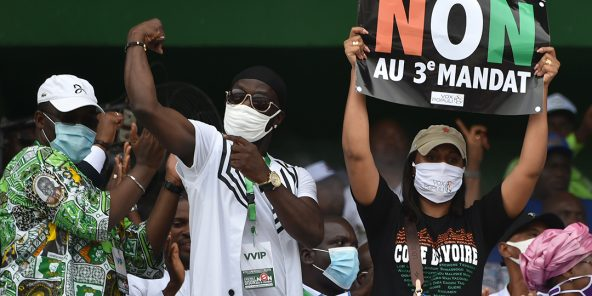"""Yasmina Ouégnin, à droite, brandit une pancarte """"Non au troisième mandat"""", lors d'un rassemblement, le 10 octobre 2020, à Abidjan."""