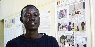 Djam's pose devant l'une de ses œuvres dans les locaux du journal «N'Djamena Hebdo», au Tchad, en novembre 2020.
