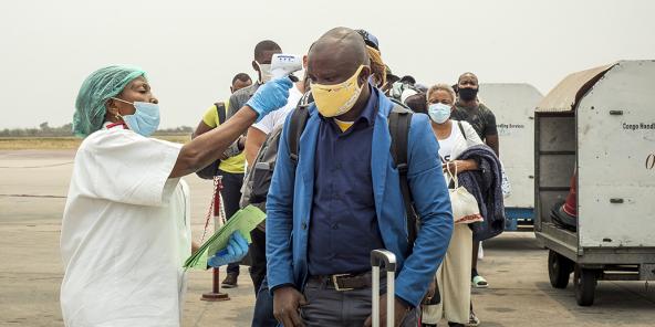 Un employé prend la température des passagers débarquant d'un vol d'Ethiopian Airlines à l'aéroport international N'Djili de Kinshasa le 15 août 2020.