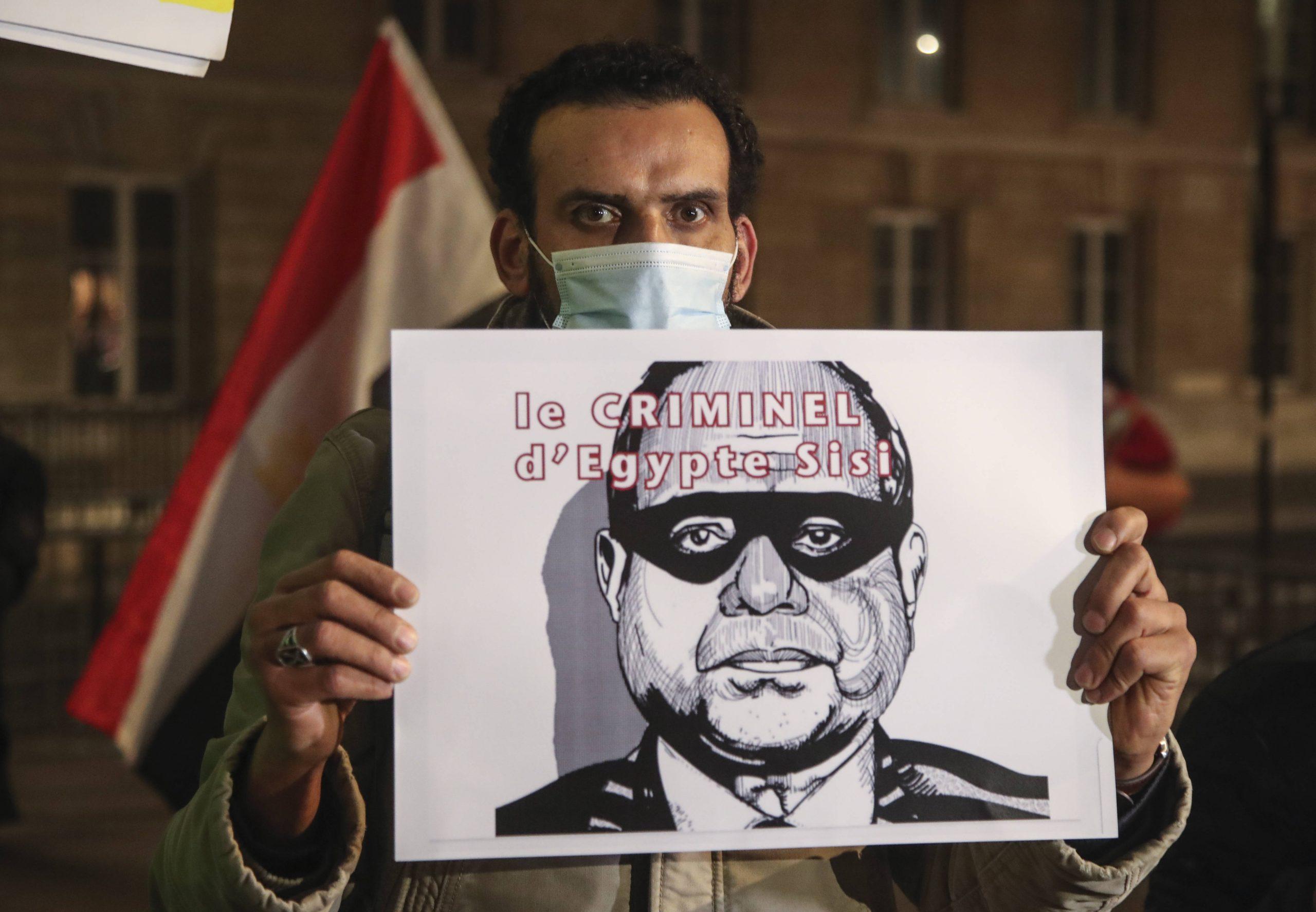 Un homme tient une pancarte représentant le président égyptien Abdel-Fattah el-Sissi à Paris, le mardi 8 décembre 2020.