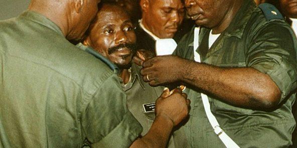 Le colonel Eddy Kapend (au centre), se voit retirer ses insignes militaires lors du procès sur l'assassinat de Laurent Désiré Kabila, le 7 janvier 2003.