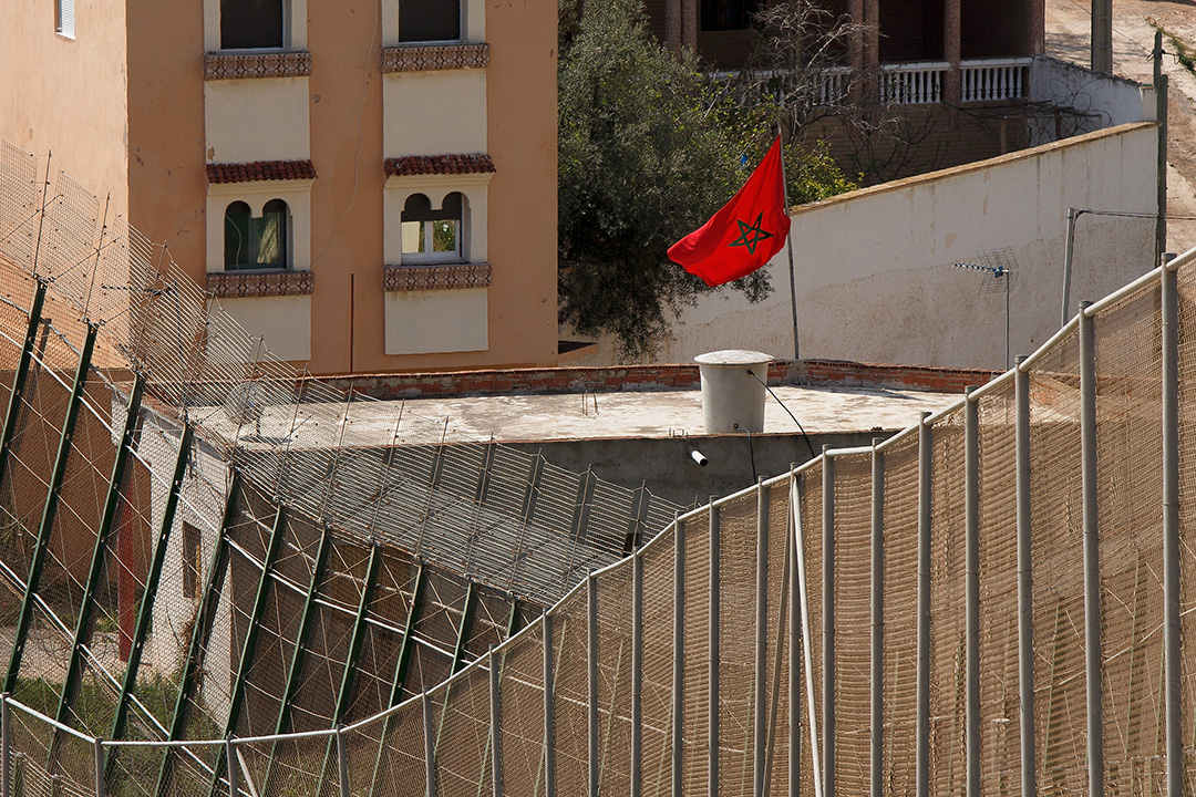 Un drapeau marocain flotte sur un bâtiment marocain derrière la clôture frontalière qui limite le Maroc de l'enclave espagnole de Melilla, le 21 mars 2014 à Melilla, en Espagne.