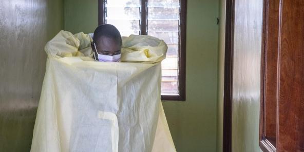 Un infirmier enfile sa combinaison de protection avant d'effectuer un test sur un patient suspecté d'être porteur du Covid-19. RDC, le 30 mars 2020.