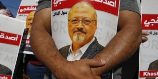 Des personnes tiennent des affiches du journaliste saoudien assassiné Jamal Khashoggi, près du consulat d'Arabie saoudite à Istanbul, marquant le deuxième anniversaire de sa mort, le 2 octobre 2020.