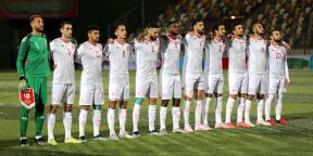 L'équipe nationale de football tunisienne chante l'hymne pendant le match de football de qualification pour la Coupe d'Afrique des Nations (AFCON) 2021 entre la Libye et la Tunisie dans la ville de Benghazi, dans l'est de la Libye, le 25 mars 2021.