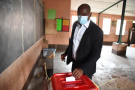 Un électeur dépose son bulletin dans un bureau de vote lors de l'élection présidentielle béninoise à Cotonou le 11 avril 2021.