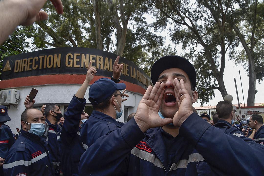Des membres de la protection civile algérienne chantent lors d'un rassemblement devant le siège du service à Alger, le 2 mai 2021.