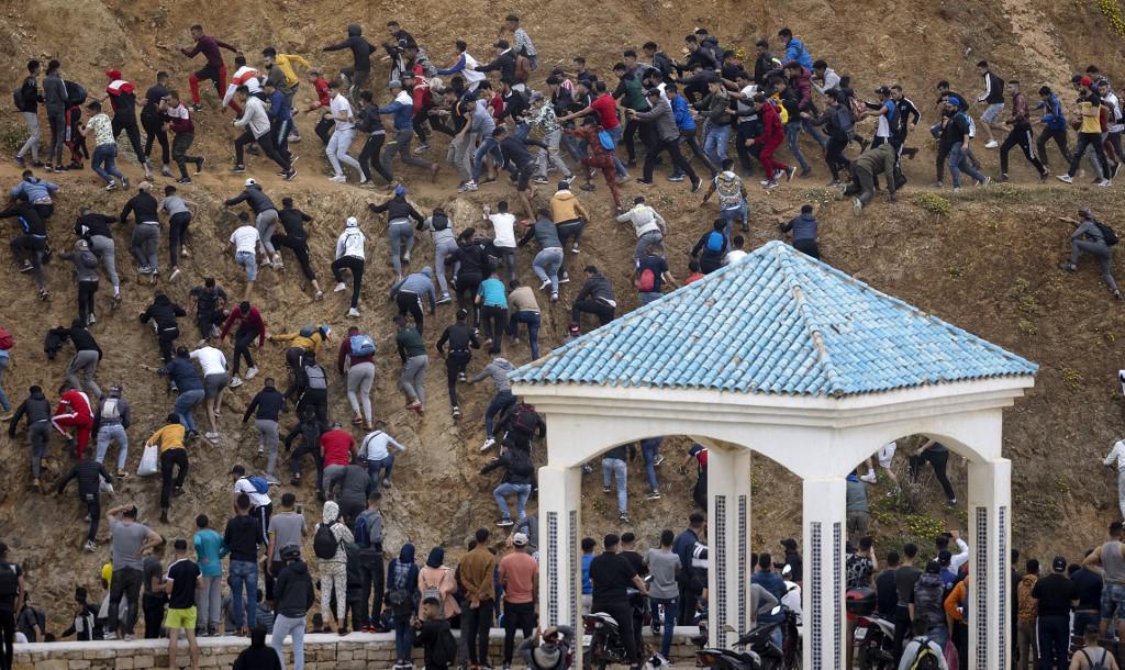 Des migrants évitent la police marocaine alors qu'ils tentent d'atteindre la frontière entre le Maroc et l'enclave espagnole de Ceuta, le 18 mai 2021 à Fnideq.