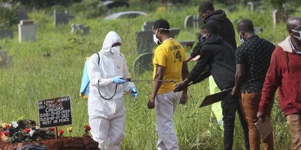 Un agent de santé désinfecte les membres de la famille lors de l'enterrement d'une personne décédée du COVID-19, à Harare, au Zimbabwe, le 15 janvier 2021.