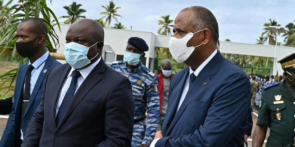 Le ministre ivoirien de la défense Tene Birahima Ouattara, le Premier ministre ivoirien Patrick Achi, accompagné par Jean-Yves Le Drian, arrivent à l'Académie internationale de lutte contre le terrorisme à Jacqueville en Côte d'Ivoire le 10 juin 2021.