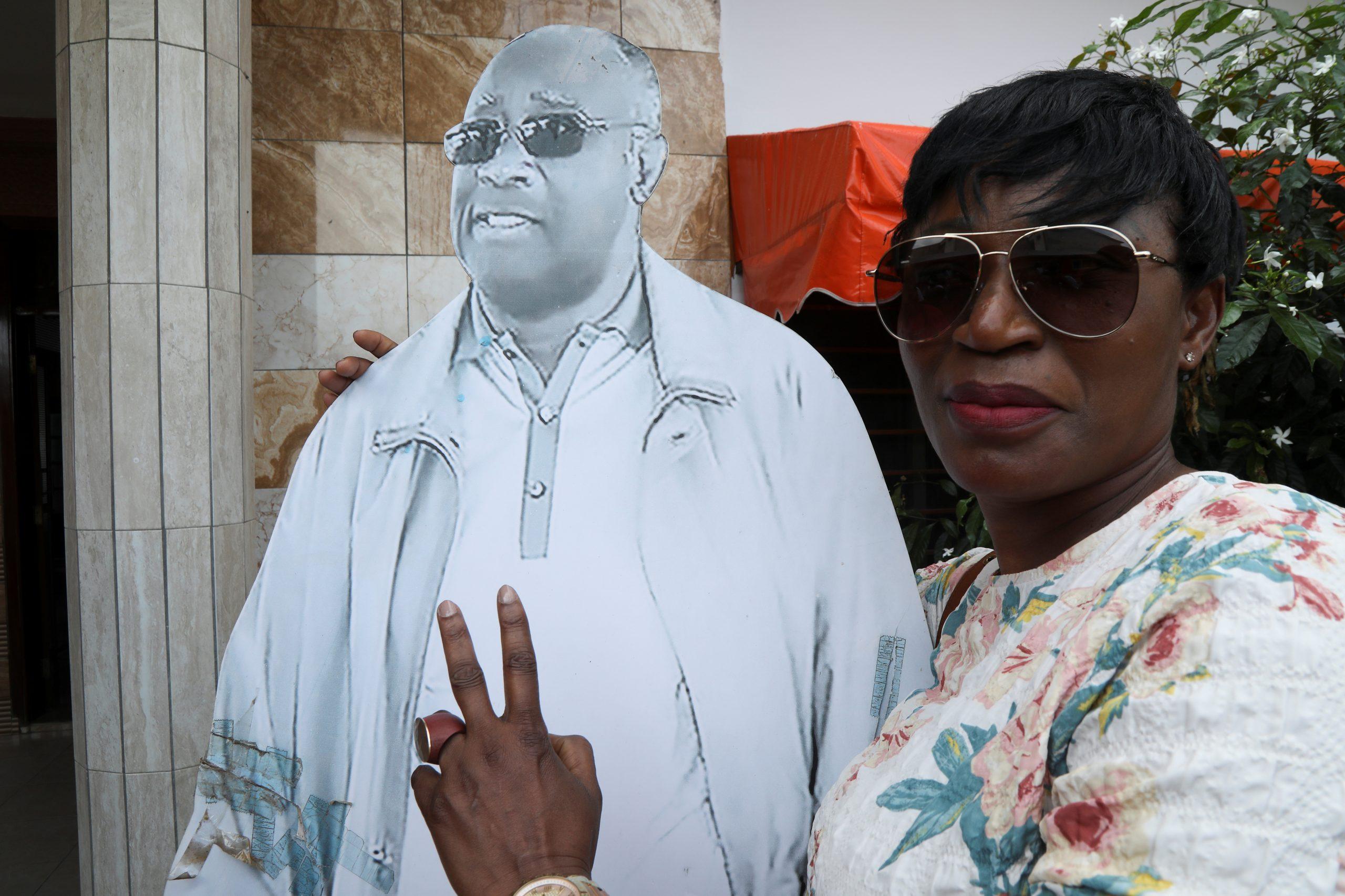 Un pro-Gbagbo pose à côté d'un portrait de l'ancien président ivoirien, au siège du FPI, le 17 juin 2021.
