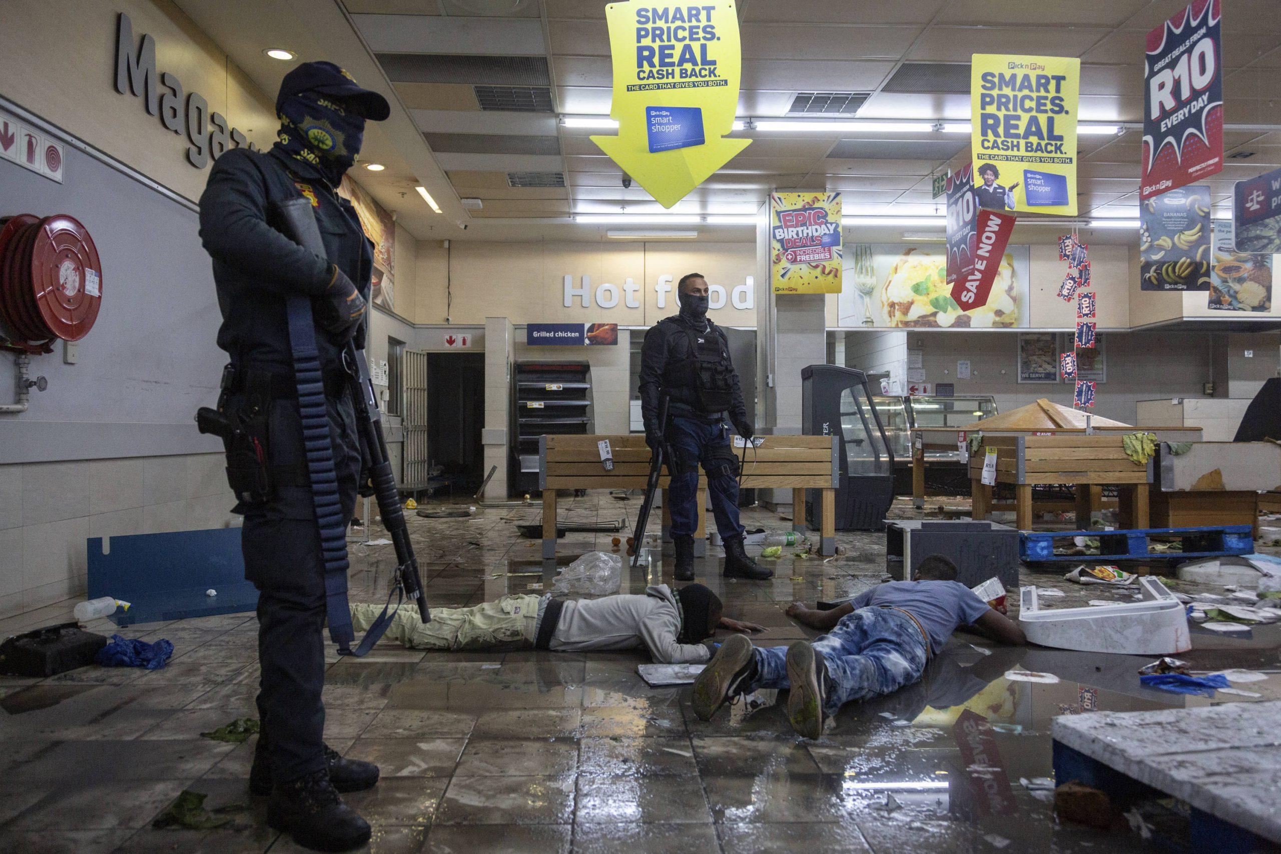 La police surveille des pilleurs arrêtés dans un centre commercial du canton d'Alexandra, à Johannesburg, en Afrique du Sud, le 12 juillet 2021.