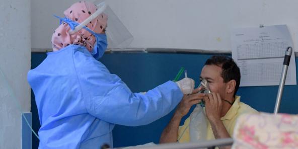 Un infirmier tunisien prodigue les premiers soins aux patients atteints de COVID-19 aux urgences de l'hôpital Charles Nicole de la capitale Tunis, le 16 juillet 2021.